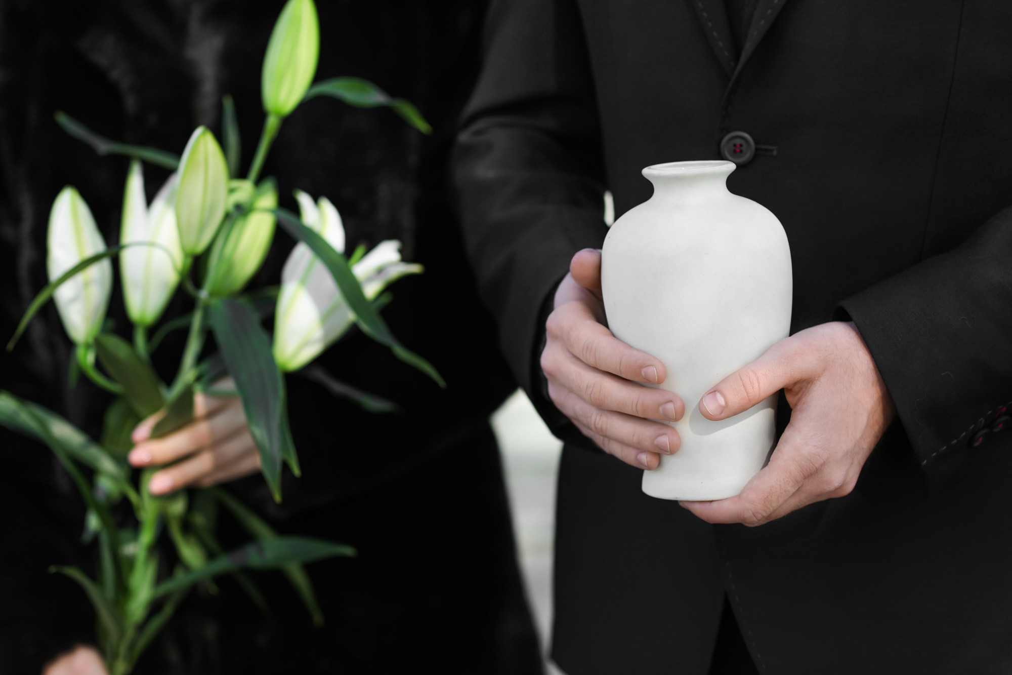 Couple with mortuary urn and flowers at cremation or burial